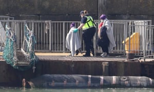 A Border Force officer helps a small child as a group of people thought to be migrants are brought into Dover, Kent