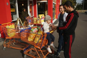 Mohamed Zayat, right, a refugee from Syria, offers sweets to his daughter Ranim