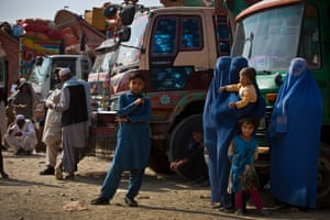 Afghan refugees, who have been forced to leave Pakistan and return to Afghanistan, stand in front of the trucks that have brought them from Pakistan at a UNHCR reception centre on the outskirts of Kabul, Afghanistan Thursday, 29 September.
