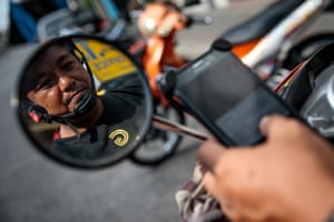 Motorbike taxi driver Poynthep Chatchawaaanamonkul, 42, loads up the Grab app on his phone