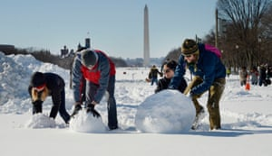 A group of friends build a snowman on the National Mall in Washington