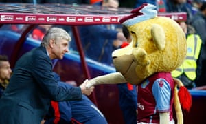 Arsenal manager Arsene Wenger shakes hands with the weloming Aston Villa mascot.