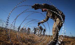Slovenian soldiers erect razorwire fences on the country's border with Croatia