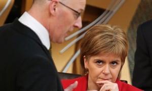 Nicola Sturgeon listens to the finance secretary, John Swinney, during first minister's questions.