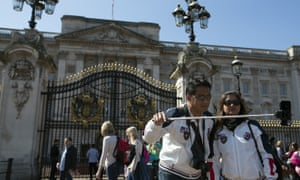 Tourists take a selfie in front of Buckingham Palace in London.