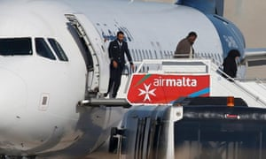 Some passengers disembark from the hijacked Libyan Afriqiyah Airways flight on the runway at Malta airport.