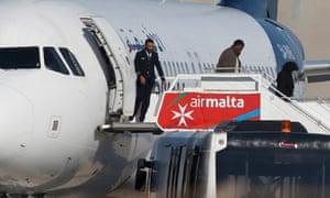 一些乘客在马耳他机场的跑道上从被劫持的利比亚Afriqiyah航空公司航班下机。
