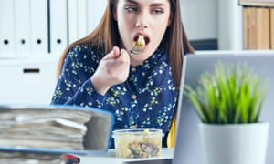 Woman eating at her office desk