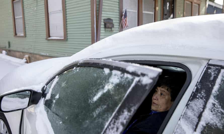 Maria Pineda uses her car to get warm in East Austin, Texas. Pineda said her home has been without power since Monday.