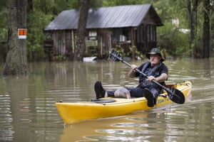 Donnie McCulley paddles out from a flooded neighborhood with an armadillo as a passenger on Thursday in Patton Village, Texas.