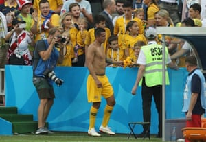 Tim Cahill of Australia gives his shirt to a young fan as he walks off dejected following his side's defeat.
