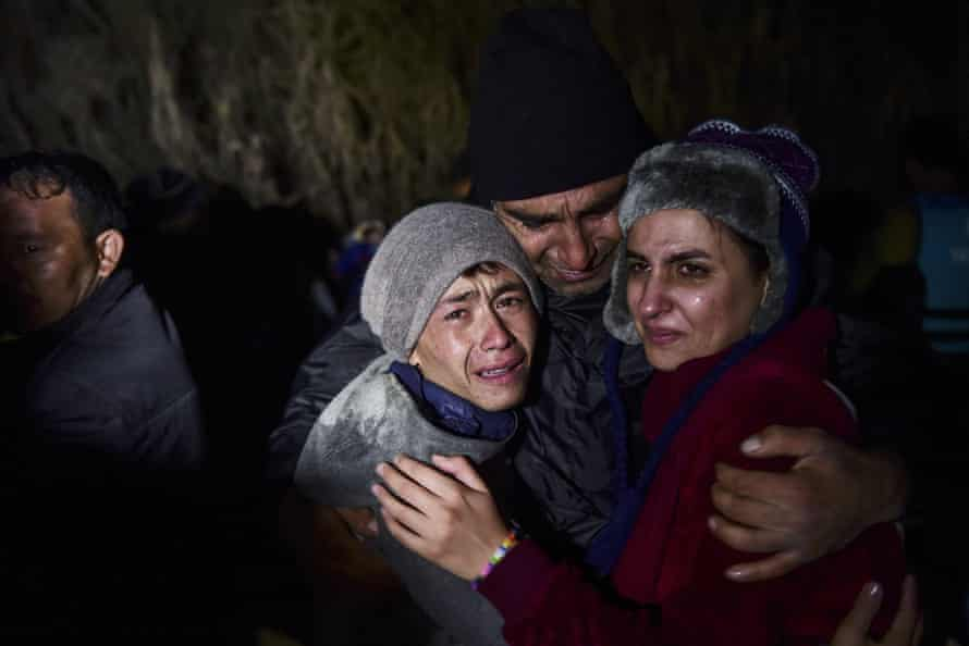 A man hugs his daughter and son on the Greek island of Lesbos.