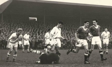Tommy Taylor and, just behind him, Denis Viollet turn away after Workington's goalkeeper makes a save during the FA Cup tie at Borough Park. Violett went on to score a hat-trick.