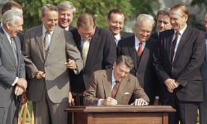 Lawmakers watch as Ronald Reagan signs a landmark tax overhaul, at the White House in Washington on 22 October 1986.
