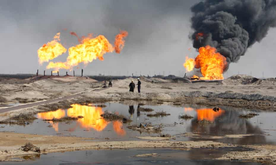 Excess gas is burned off near workers at the Rumala oil field, south of Basra. Plunging oil prices leaves Iraq's revenues in jeopardy.