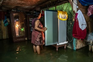 Sutarti checks her fridgee in the kitchen of her flooded home. She does not have enough money to move to a safe place.
