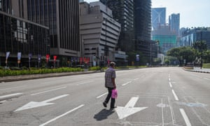 A man walks on an empty street during day three of movement control order (MCO) enforcement in Kuala Lumpur, Malaysia