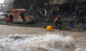 Water floods the road after an air strike hit a water pipeline in Aleppo. Residents of the city suffer frequent cuts in water supply.