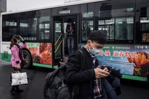 Residents get out of a bus in Wuhan, China, on Wednesday after the public transport was partly resumed in the city