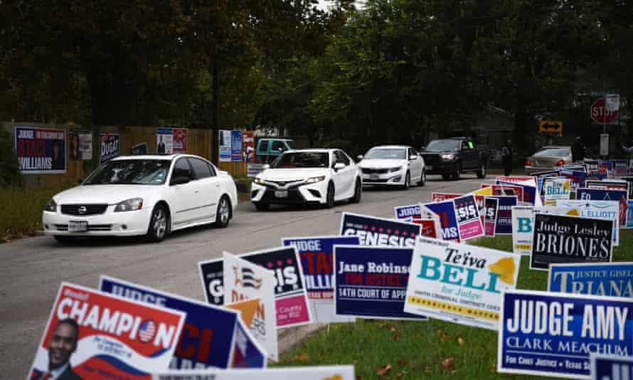 A line of cars drive in for an event encouraging community members to vote in the upcoming election at an early voting site in Houston, Texas, on 25 October.