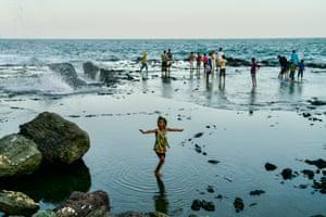 Girl plays in the water on Serra beach, near Aden