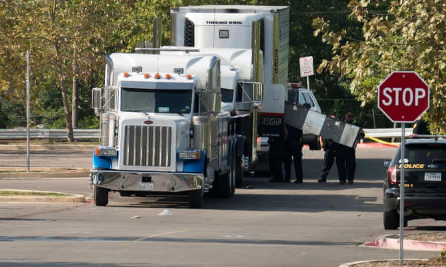 Officials tow a truck that was found to contain 38 suspected illegal immigrants in San Antonio, Texas. Eight of the people died at the scene, and 17 were transported to area hospitals with life-threatening injuries. Later, two more people died in hospital.