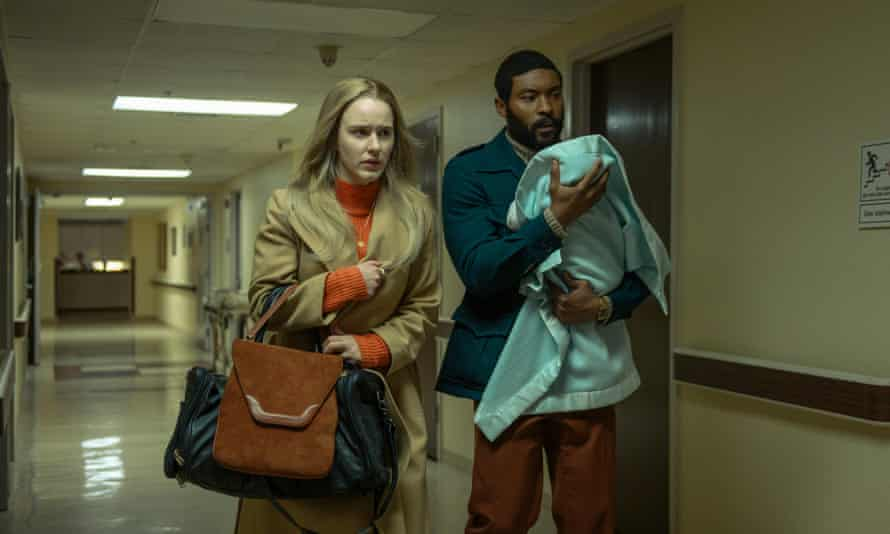 Rachel Brosnahan looking anxious with Arinzé Kene carrying a swaddled baby, walking down a hallway in a scene from I'm Your Woman.