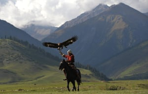 A mounted Kyrgyz berkutchi (an eagle hunter) holds his golden eagle during the World Nomad Games