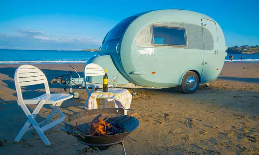 a vehicle from Barefoot Caravans parked on the beach with a table set for two