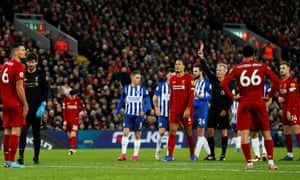 Referee Martin Atkinson shows Liverpool goalkeeper Alisson, second left, a straight red card at Anfield.