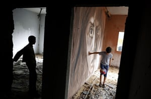 A boy plays football next to a mural painted by Palestinian artist Ali Al-Jabali on the remains of a building that was partially destroyed during the 2014 war between Israel and Hamas.