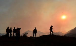 Firefighters position themselves on a ridge overlooking flames from the Bobcat Fire in a valley below in the Angeles national forest on Wednesday.