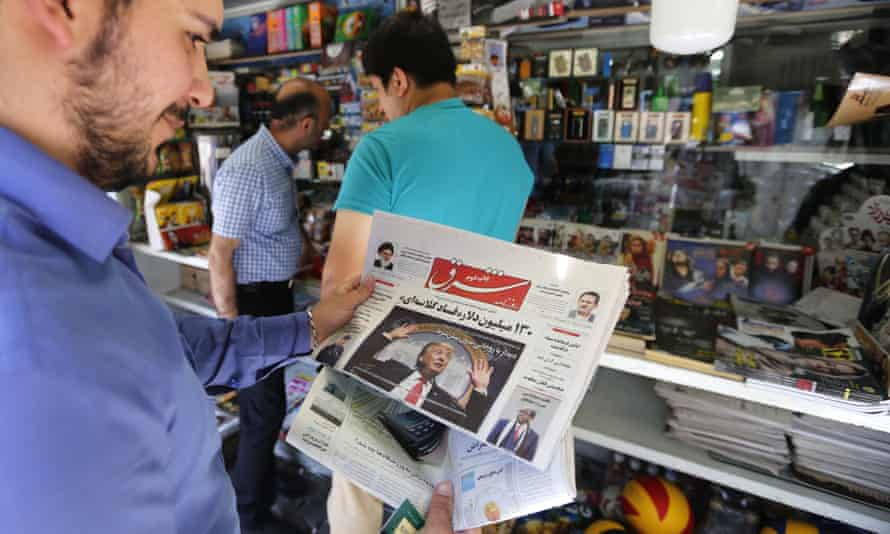 A Tehran man looks at a newspaper with the US president, Donald Trump, on the front page.