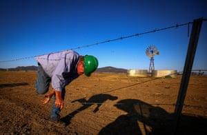 Owen Tydd goes through a fence to inspect a windmill near Gunnedah in New South Wales, Australia