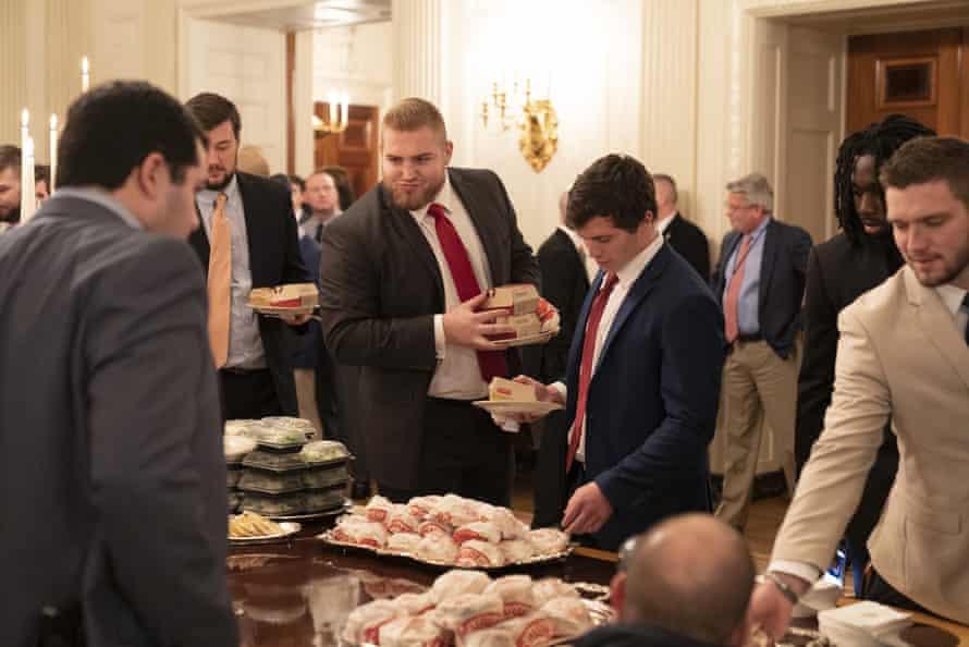 Members of the Clemson Tigers football team grab their burgers