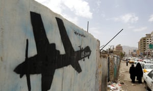 Yemenis walk past graffiti showing a US drone.