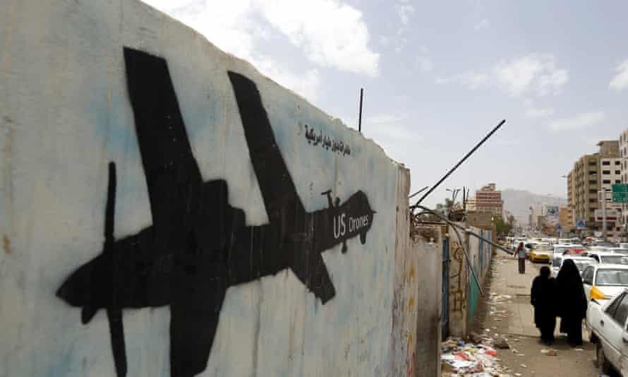 Yemenis walk past graffiti showing a US drone.