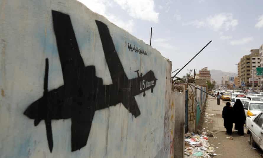 Yemenis walk past graffiti showing a US drone