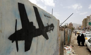 Yemenis walk past graffiti showing a US drone last year.