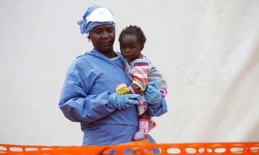 Victorine Siherya, an Ebola survivor working as a caregiver to babies who are confirmed Ebola cases, holds an infant outside the red zone at the Ebola treatment centre in Butembo