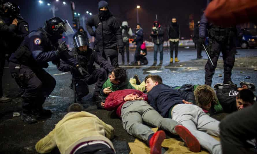 Riot police detain protesters during a protest in front of the government headquarters.