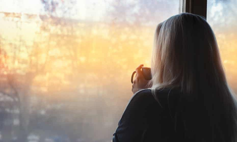 A woman stands by a window holding a hot drink