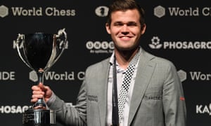 Magnus Carlsen poses with the trophy after winning the world chess championship against Fabiano Caruana.