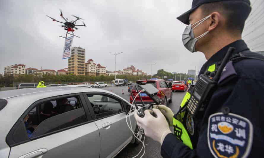 A police officer operates a drone carrying a QR code for drivers to register their vehicles online when entering Shenzhen, China.