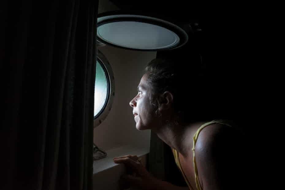Laurence Nicoud from France, the only female cook for the Rainbow Warrior III, checks the weather from the porthole of her cabin before starting meal preparations for the day. Crew cabins are kept warm via recycled heat generated from the engine and water used from showering is treated and purified by a biological system