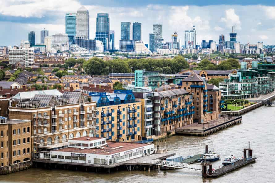 A City of London panoramic view featuring skyscrapers of the Isle of Dogs with Canary Wharf in the distance. In the foreground we can see the river Thames and the old wharves that have now been converted into luxury apartments and residential areas