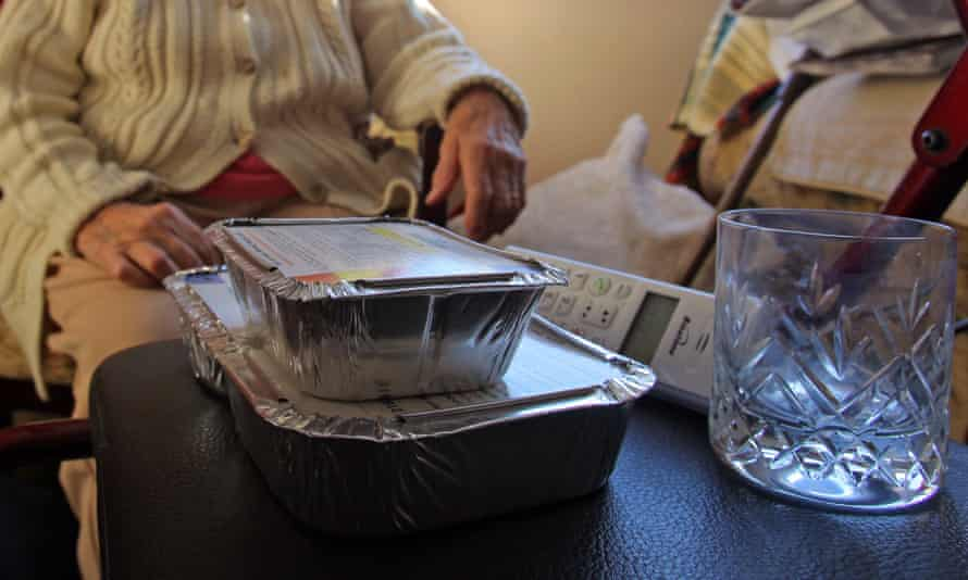 A meals-on-wheels delivery to an elderly woman