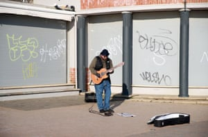 A busker plays on the deserted streets at Brighton beach.