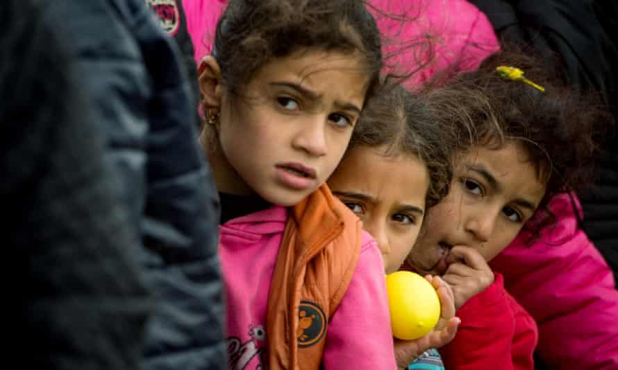 Children queue for food at a makeshift migrant and refugee camp on the Greek-Macedonian border.