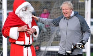 Boris Johnson in goalkeeper kit standing in goal with man in Santa costume